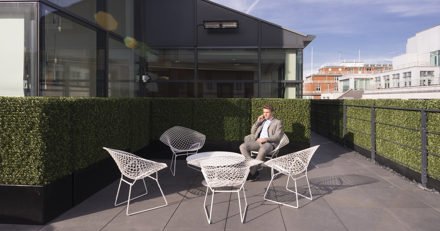 Sunny exterior view of man using phone on terrace