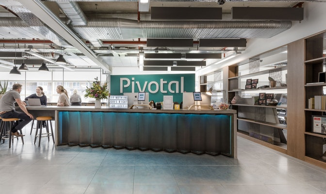 Green reception space at Pivotal Software with people at collaborative seating