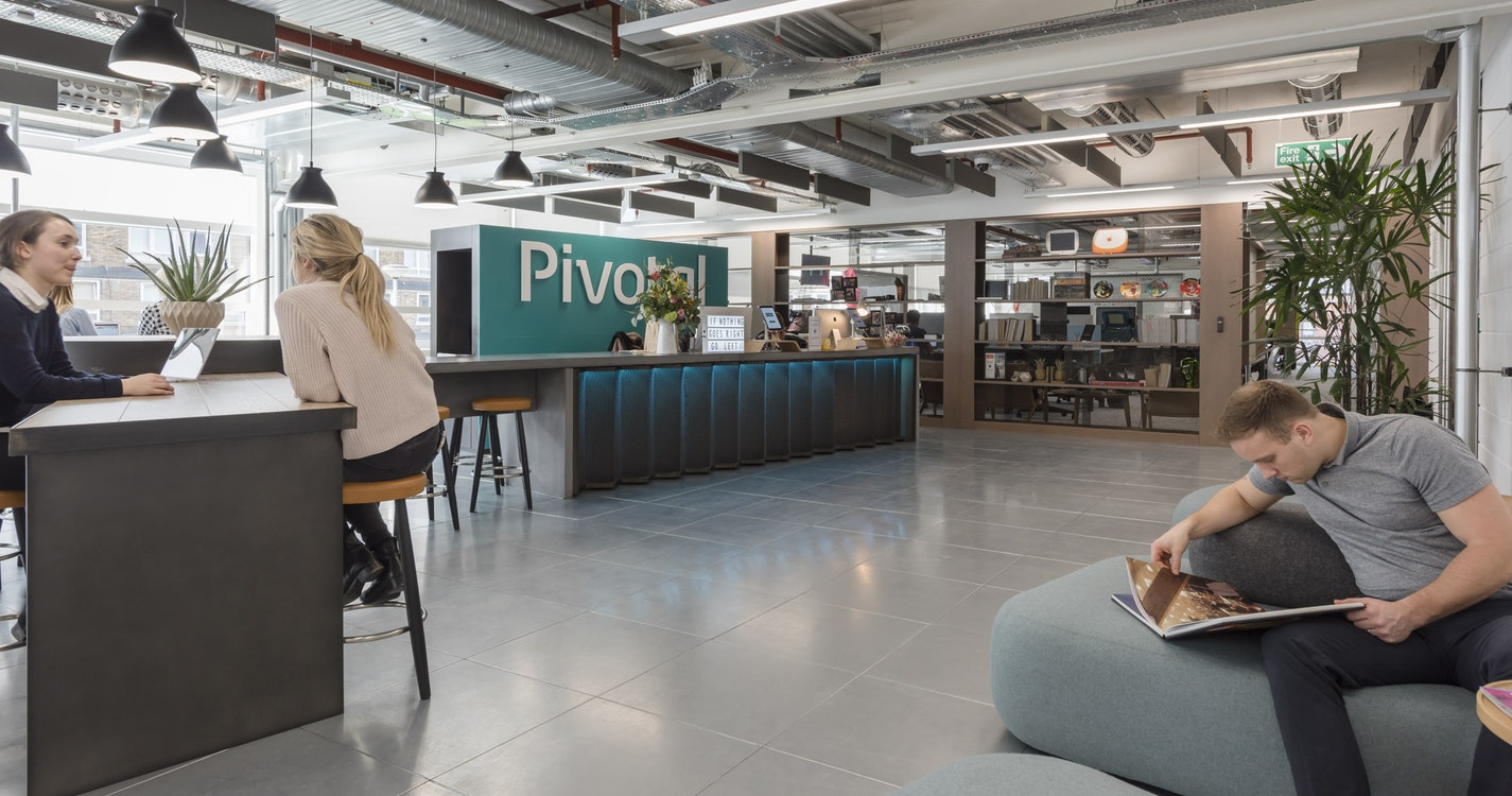 Pivotal Software reception space with casual seating and man reading magazine