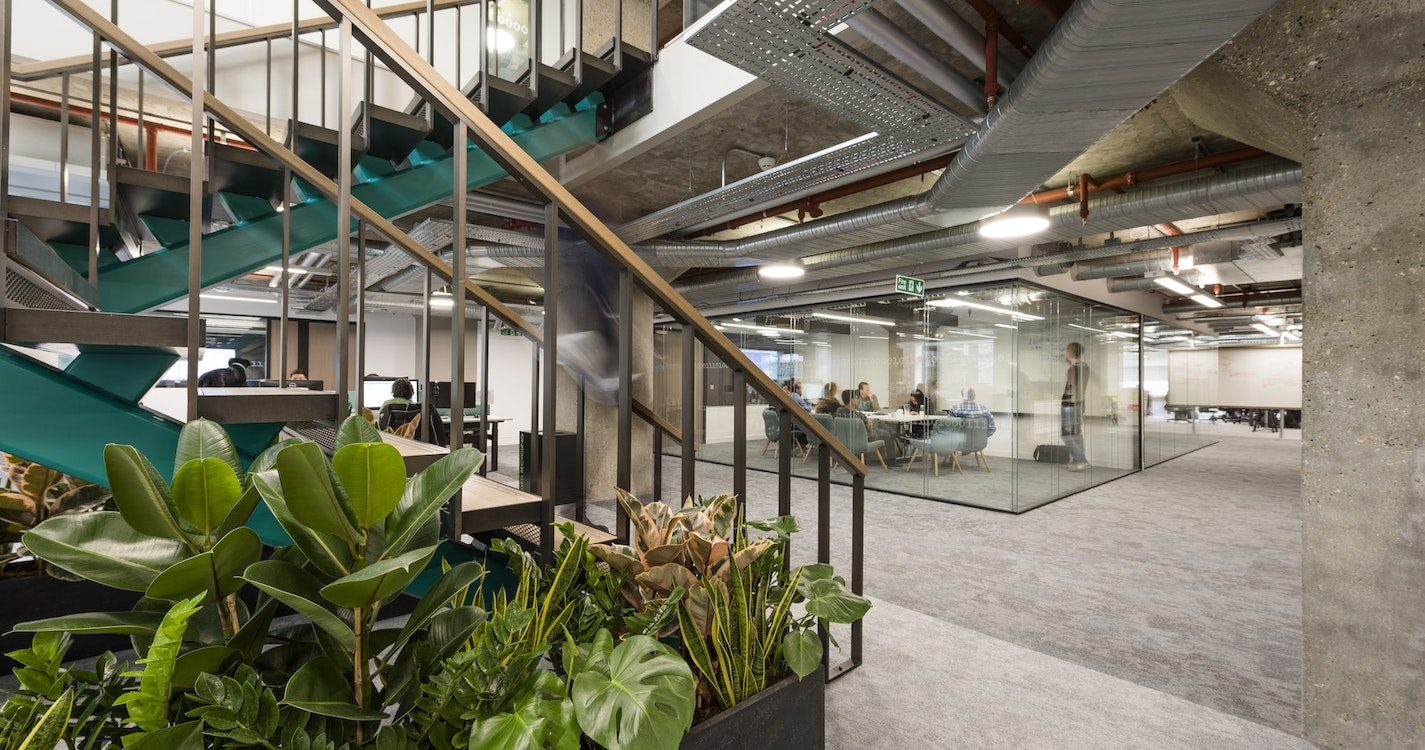 Staircase connecting two floors of work environment and surrounded by plants