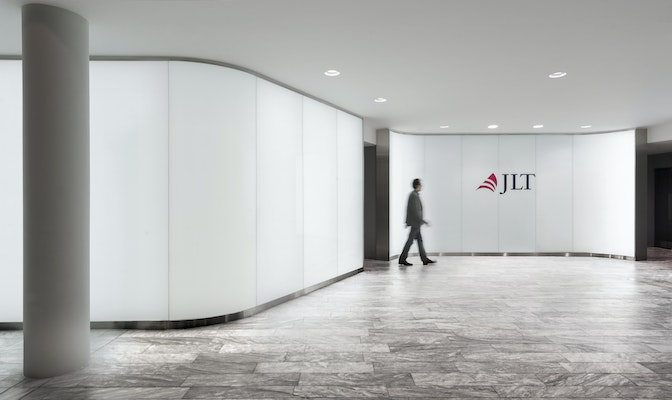 Man walking across lightbox wall with JLT branding