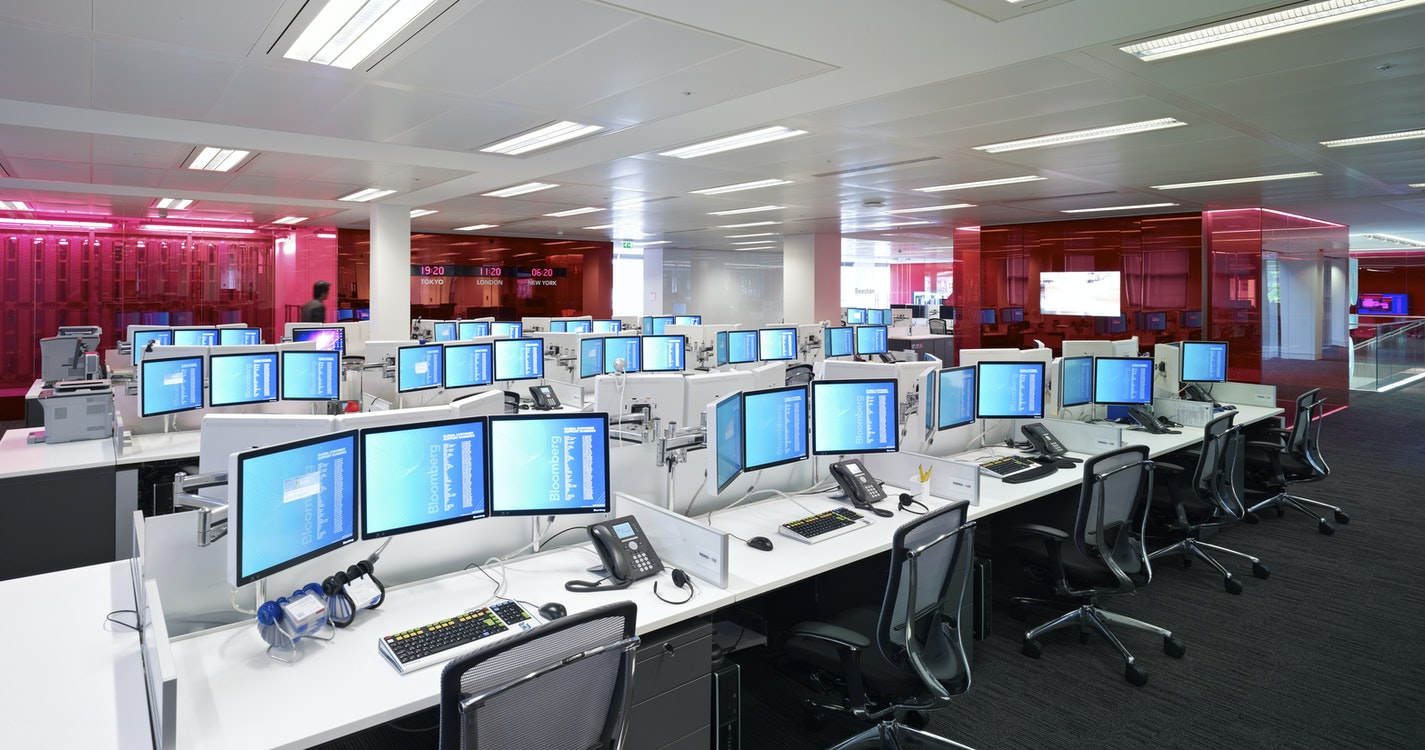 Rows of desks with coloured glass meeting rooms
