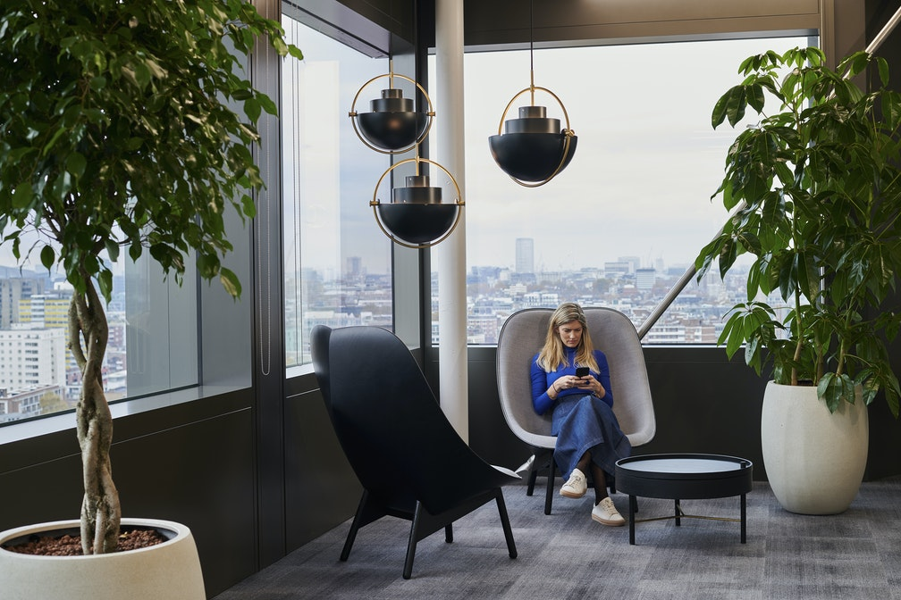 woman sitting in chairs by window in office with overhead hanging lights