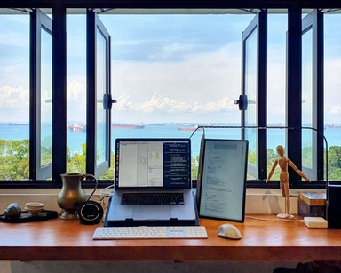 Working from home laptop on desk with view onto Singapore bay