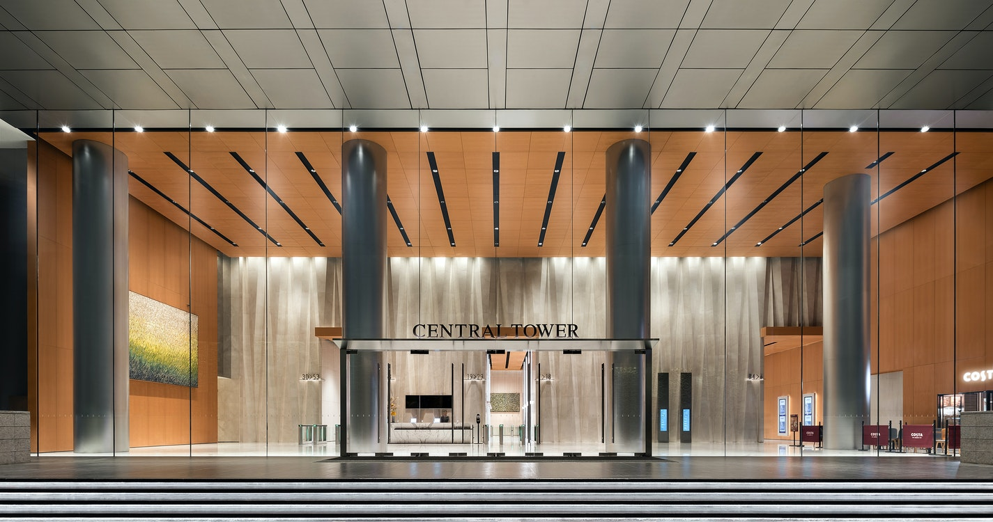 Spacious office tower entrance with large columns, artworks, and public café