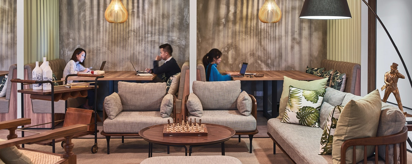 people working in booths in lounge seating space