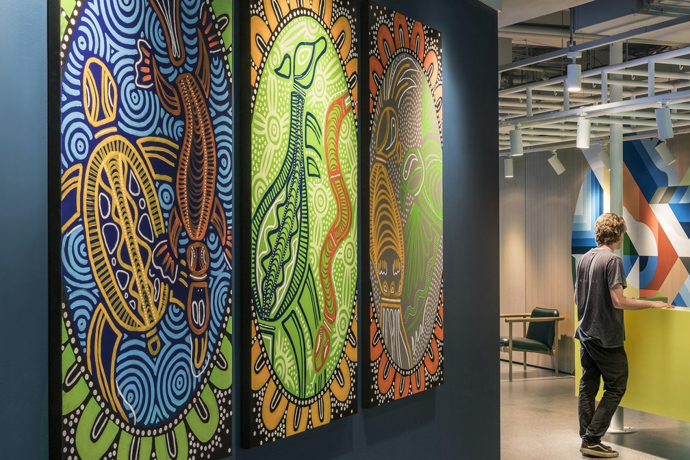 Aboriginal artworks in office corridor leading to spacious reception featuring a creative mural