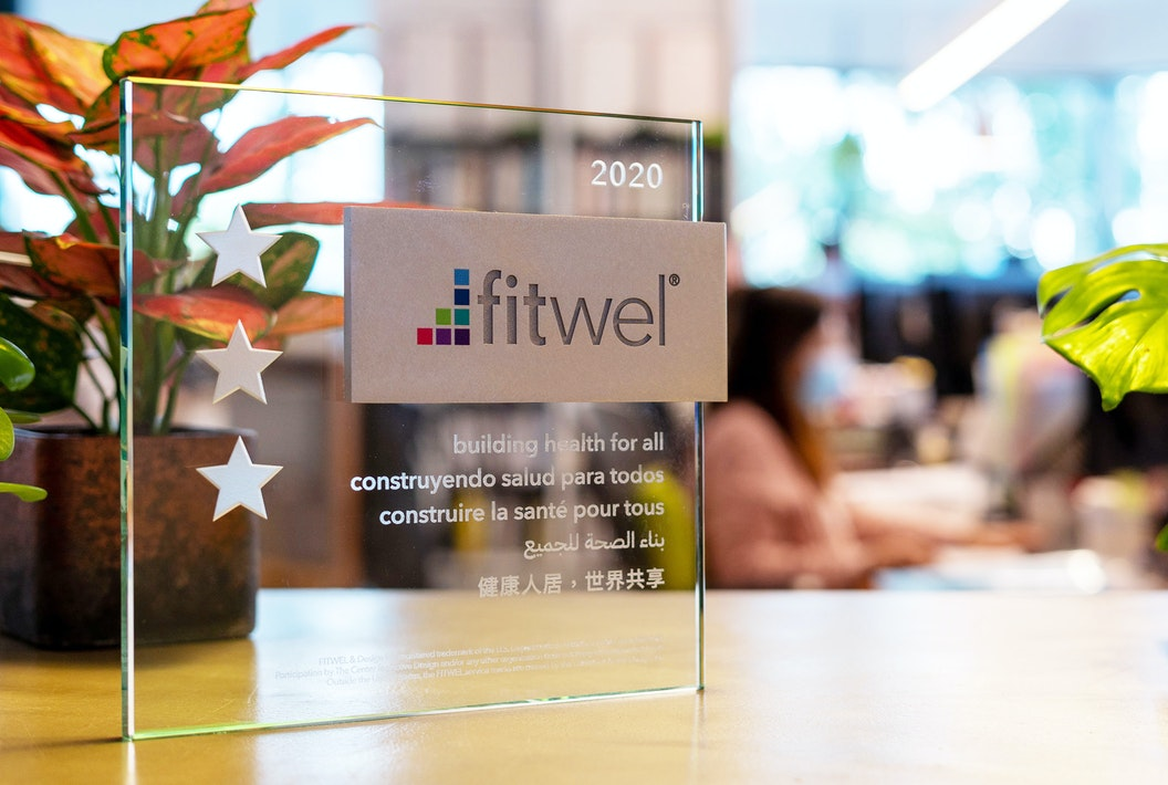 Fitwel certificate displayed on wooden table with plants